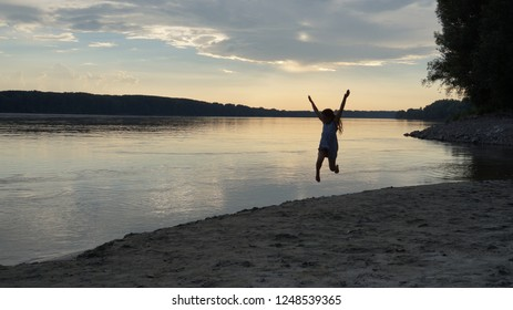 the child runs and jumps on a sandy beach as the sun sets