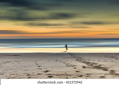 A child runs toward the sea at sunset in a loneliness beach