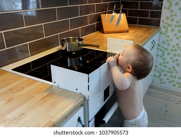 Child safety at the stove. A little baby child is curious and watching a hot pot on a stove.