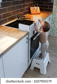 Child safety at the stove. A little baby child is curious and tries to take a hot pot on a stove.