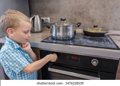 Child safety at the stove. A little boy is curious and play with hot oven.