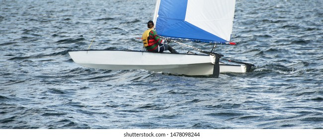 Child sailing in small colourful catamaran boat with a blue and white sail on an inland waterway. Junior sailor competing racing on saltwater Lake Macquarie. Photo for commercial use.