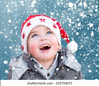 Child with Santa Claus Christmas hat looking at snow falling