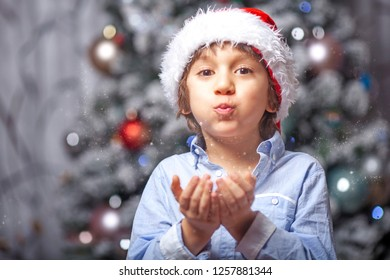 Child with Santa Claus hat close to a Christmas tree