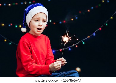 A child in a Santa Claus hat and in a red sweater on a black background holds a sparkler in his hands. Scared child. Danger Safety measures for the New Year and Christmas. holidays, holiday concept