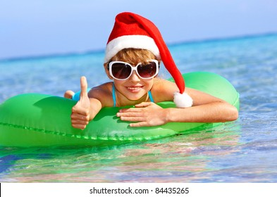 Child in santa hat  floating on inflatable ring in sea. Thumb up.