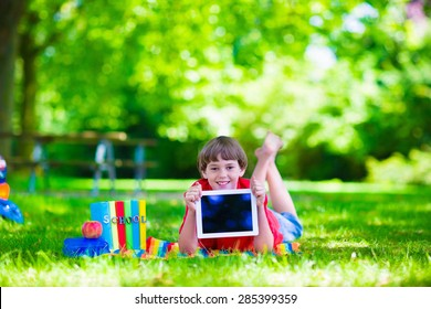 Child in school with tablet PC. Smart teenager student boy studying and learning outdoors, reading books. Children doing homework research on the internet with modern computer. Kids with gadgets.