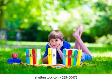 Child in school yard. Smart teenager student boy studying and learning outdoors, reading books and having apple for healthy snack. Kids happy to be back to school. Children in a class.