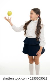 Child schoolgirl wear formal uniform hold apple. Girl cute pupil hold apple fruit stand on white background. Kid happy hold apple. School snack concept. Healthy nutrition diet. Apple vitamin snack.