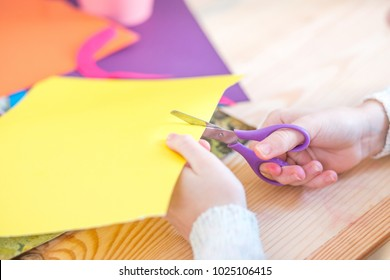 Child with scissors cut paper