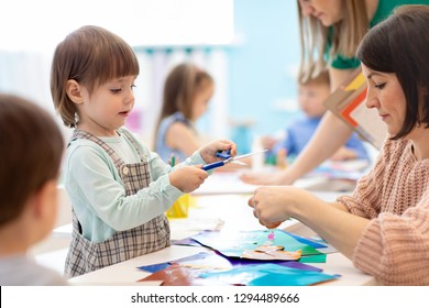 Child with scissors in hands cutting paper with teachers in class room. Group of children doing project in kindergarten. Kids play into team.