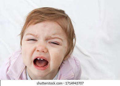 The child screams with his mouth open. Negative emotions of the child. Vagaries and crying baby.