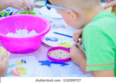 child sculpts figures from plasticine. development center. help children with disabilities. A pretty girl of three years old sits at the table and sculpts figures from colored clay. Sculpting and
