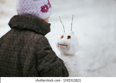 The child sculpts funny snowman in winter Park. Child playing with snow. Kid sculpts big snowman. Children wintertime outdoor activity time concept.