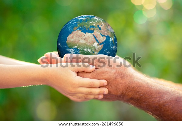 Child and senior holding planet in hands against green spring background. Earth day holiday concept. Elements of this image furnished by NASA