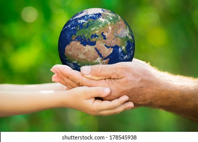Child and senior man holding Earth in hands against green spring background. Elements of this image furnished by NASA