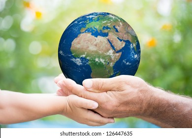 Child and senior man holding planet Earth in hands against green spring background. Elements of this image furnished by NASA