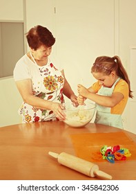 Child and senior woman baking cookies for Christmas in vintage look