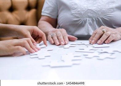 Child and senior woman playing with puzzle pieces on white table.Exercise for brain development.Retirement and holiday amusement.