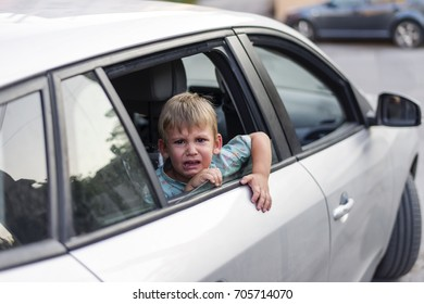 child separated from one parent leaving in a car, sad and crying
