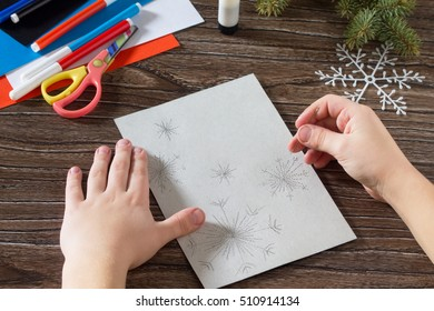 Child sewing needle details paper snowflakes. The child makes a greeting card with a snowman. Glue, paper, scissors on a wooden table. Children's art project, a craft for children.