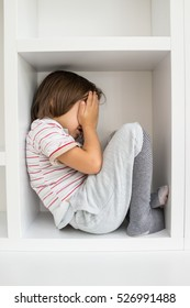Child in shelf inside living room