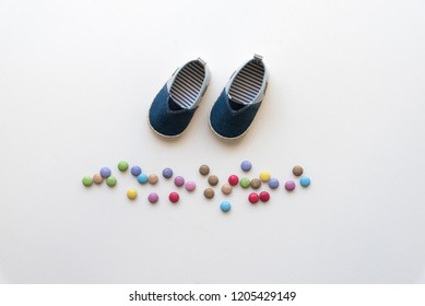 Child shoes and candies on a white background.