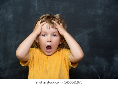 Child shouting loud standing in class against blackboard. Stylish pupil holding hands on head. Portrait of shocked, angry and emotional little kid. Back to school