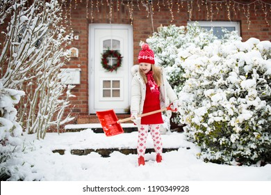 Child shoveling snow. Little girl with spade clearing driveway after winter snowstorm. Kids clear path to house door after Christmas blizzard. Snowfall fun. Children play in cold frosty garden.