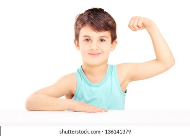 A child showing his muscles seated on a table isolated on white background