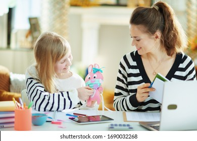 child showing mother pink toy rabbit in medical mask in temporary home office in the modern house in sunny day.