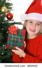 Child showing a present by the Christmas tree