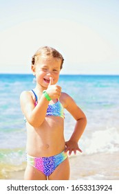 Child shows thumb up symbol. Little girl resting on the beach.