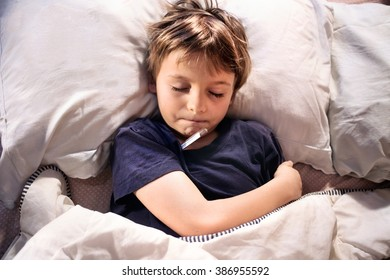 child sick in bed sleeping and testing fever