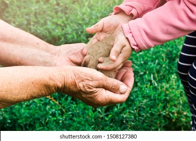 A child sifts sand in the palm of his old grandmother. Sand seeps through children's fingers into the hands of an old grandmother. Baby and old hands close-up