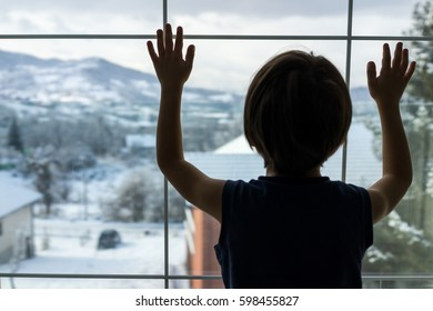 Child silhouette standing on home window