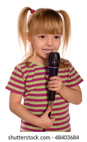 Child singing with a microphone. Funny little girl isolated on white background. Beautiful caucasian model.