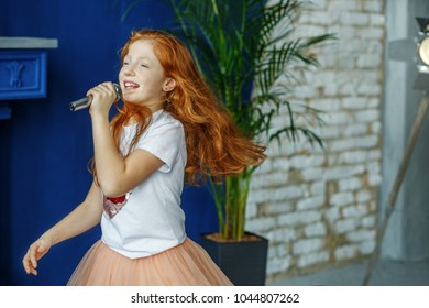 The child sings the song in the microphone. Very long hair. The concept is childhood, lifestyle, music, singing, listening, hobbies.