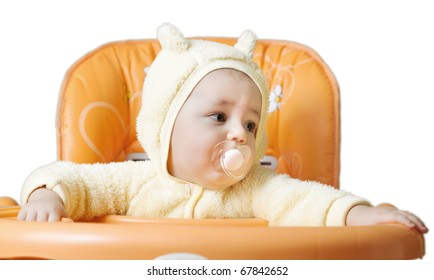 The child sits in a baby chair isolated on white background