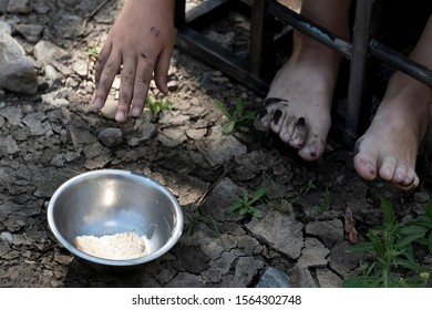 The child sits in a cage and pulls his hand through the bars of an iron grate to a piece of bread in a metal plate. The concept of slavery, hunger, violence and child trafficking. Violation of the law