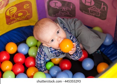 The child sits in the game room in the arena with colorful balls and chewing on them, because he is teething or hungry