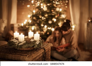 Child sits with mother in front of the Christmas tree and read a book together and look forward to X-Mas, advent wreath - Shutterstock ID 1848547474