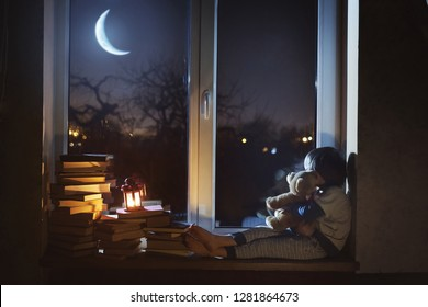 The child sits at night on the windowsill, hugs a toy and looks at the young moon.
