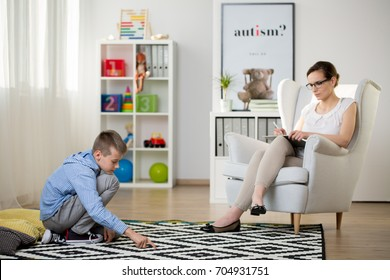 Child sits on black and white carpet while psychotherapist is observing him. Autistic child therapy concept