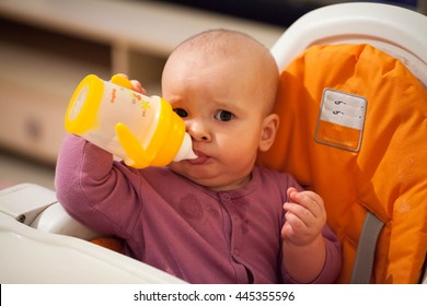 The child sits on a high chair and drinking water from a feeder cup