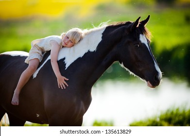Child sits on a horse in meadow near small river.