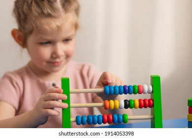 The child sits at the table, counts and smiles. Children's wooden toy. Educational logic toys for children. Close-up of hands. Montessori games for child development. Selective focus.