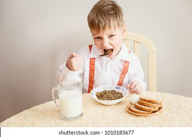 the child sits at the table and eats the lentils, healthy eating, milk, eggs, bread