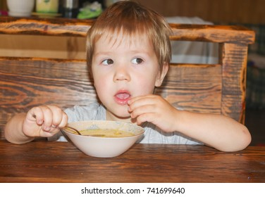 The child sits at the table and eats from a plate on their own. Little boy eats from a plate. The child eats with a spoon.