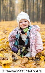 A child sitting in autumn leaves in doubt